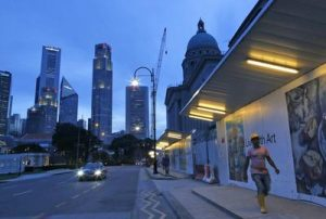 A foreign construction worker from Bangladesh walks past Singapore's city hall with the Singapore skyline in the background, 16 December 2013. (Photo: AAP)