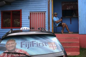 """An election poster for Voreqe """"Frank"""" Bainimarama can be seen in the rear window of a taxi as a man gestures from the doorway of a local gymnasium in the Fiji capital of Suva. (Photo: Reuters)."""