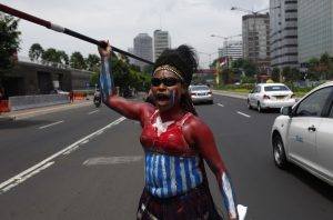 A West Papuan woman dances with her spear during a protest (Photo: Reuters).