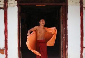A Buddhist monk smiles as he adjusts his robe while speaking with his friend at a monastery in Yangon 13 March 2012 (Photo: Reuters).