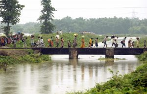 Flood-affected people carrying their belongings move to safer places at Madhepura town in India's eastern state of Bihar, 29 August 2008 (Photo: Reuters/Krishna Murari Kishan).