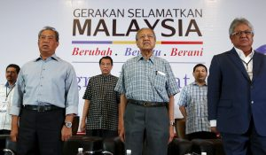 Malaysia's former deputy prime minister Muhyiddin Yassin, former prime minister Mahathir Mohamad and former minister Zaid Ibrahim stand for the national anthem during a meeting of political and civil leaders looking to change the government in Kuala Lumpur, Malaysia (Photo: Reuters/Olivia Harris).