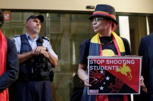 An Australian Federal Policeman guards the entrance during a demonstration against police violence earlier in the week against university students in Port Moresby, outside the Papua New Guinea Consulate in Sydney, Australia, 10 June 2016. (Photo: Reuters/Jason Reed)