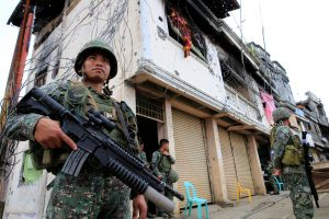 Government soldiers stand guard in front of damaged building and houses in Sultan Omar Dianalan boulevard at Mapandi district in Marawi city, southern Philippines, 13 September 2017 (Picture: Reuters/Romeo Ranoco).