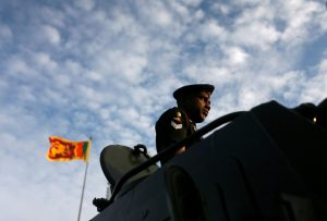 An Army soldier looks on from a tank, as Sri Lanka's national flag is seen in the background, at the parade during a rehearsal for Sri Lanka's 70th Independence day celebrations in Colombo, Sri Lanka, 1 February 2018 (Photo: Reuters/Dinuka Liyanawatte).
