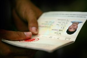 A Solomon Islander of Chinese descent holds his passport as officials organise flights to China for people targeted by rioters in Honiara, Solomon Islands, 23 April 2006 (Photo: Reuters/Tim Wimborne).