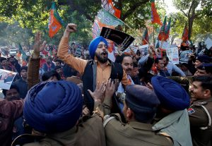 A supporter of India's ruling Bharatiya Janata Party (BJP) shouts slogans as he is stopped by police during a protest against what they call 'disinformation' by India's main opposition Congress party on a deal to buy Rafale fighter planes from a French company, in Chandigarh, India, 19 December 2018 (Photo: Reuters/Ajay Verma).