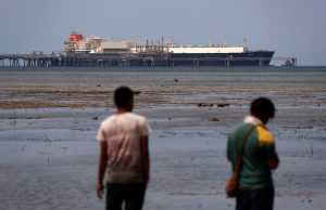Locals walk along a small beach where a Liquefied Natural Gas carrier called Kumul is docked at the marine facility of the ExxonMobil PNG Limited operated LNG plant at Caution Bay, located on the outskirts of Port Moresby in Papua New Guinea, 19 November 2018 (Photo: Reuters/David Gray).