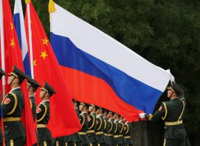 A military officer adjusts a Russian flag ahead of a welcome ceremony hosted by Chinese President Xi Jinping for Russian President Vladimir Putin outside the Great Hall of the People in Beijing, China, 8 June 2018 (Photo: Reuters/Jason Lee).