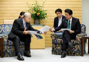 Angel Gurria (L), Secretary-General of the OECD shows reports about the G20 to Japanese Prime Minister Shinzo Abe (R) in Tokyo, Japan, 15 April 2019 (Photo: Kimimasa Mayama/Pool via REUTERS).