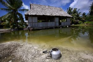 An abandoned house that is affected by seawater during high-tides stands next to a small lagoon near the village of Tangintebu, South Tarawa, Kiribati, 25 May 2013 (Photo: Reuters/David Gray).
