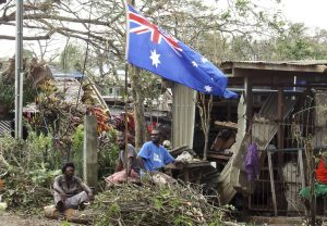 Local residents sit outside their damaged homes surrounded by debris on a street after Cyclone Pam hit Port Vila, Vanuatu, 15 March 2015. (Photo: Reuters/Kris Paras)
