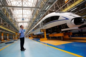 A worker stands next to a high-speed train at the maintenance and repair depot of China Railway High-speed (CRH) rail service during a media tour in Beijing, China, 30 August 2018. (Photo: Reuters/Thomas Peter).