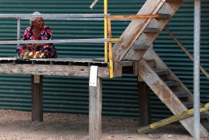 A woman sits on a staircase at her house located near the ExxonMobil PNG Limited operated Liquefied Natural Gas plant in the village of Papa Lea Lea located at Caution Bay on the outskirts of Port Moresby, Papua New Guinea, 19 November 2018 (Photo: Reuters/David Gray).