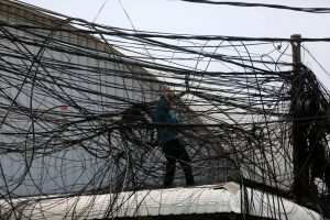 An electrician prepares electrical wires along a street in Phnom Penh,Cambodia, 23 April 2018 (Photo: Reuters/Samrang Pring).