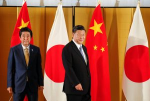 Chinese President Xi Jinping and Japanese Prime Minister Shinzo Abe look at media as they walk into the venue of their talks at a Osaka hotel, prior to the G20 Summit at the International Exhibition Center in Osaka, western Japan, 27 June 2019 (Photo: Reuters/Kimimasa Mayama).