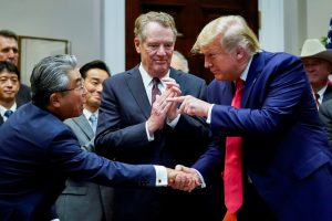 US President Donald Trump shakes hands with Japan's Ambassador to the United States Shinsuke Sugiyama in front of US Trade Representative Robert Lighthizer during a formal signing ceremony for the US-Japan Trade Agreement at the White House in Washington, 7 October 2019 (Photo: Reuters/Kevin Lamarque).
