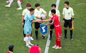 Je Yong-Sam (front L), captain of aSouthKoreanworkers' soccer team gives a Korean unification flag to Kang Jin-Hyuk, captain of aNorthKoreanworkers' soccer team before their inter-Koreanfriendly soccer match at the Seoul World Cup Stadium in Seoul,SouthKorea, 11 Aug 2018 (Photo: Reuters/Lee Jae-Won).