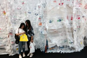 Tourists hold up their plastic bags as they stand next to the art installation 'A Bangkok Minute' made of plastic bags during an event organised by the United Nations Environment Programme at a department store in central Bangkok, Thailand, 5 June 2018 (Photo: Reuters/Athit Perawongmetha).