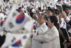 South Korean President Moon Jae-in and his wife Kim Jung-sook wave national flags during a ceremony to mark the 74th anniversary of Korea's liberation from Japan's 1910-45 rule, Choenan, South Korea, 15 August 2019 (Photo: Reuters/Jung Yeon-je).