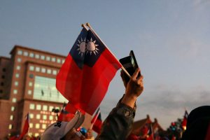A Kuomintang party supporter holds Taiwanese flags before an election rally in Taipei, Taiwan, 9 January 2020 (Photo: Reuters/Ann Wang).