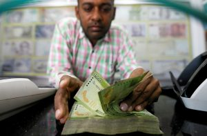 A man counts Sri Lankan rupees notes at a counter of a currency exchange shop in Colombo, Sri Lanka, 14 November 2017 (Photo: Reuters/Dinuka Liyanawatte).