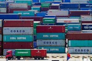 A truck carrying containers are seen near a Chinese flag at the Yangshan Deep Water Port in Shanghai, China, 6 August 2019 (Photo: REUTERS/Aly Song).