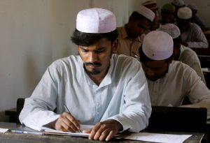 A student of a madrassa (religious school) writes during an examination in Kolkata, eastern India, 7 March 2006 (Photo: Reuters/Jayanta Shaw).