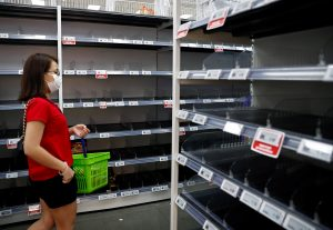 A woman wearing a protective mask passes empty shelves of instant noodles and canned food, as people initially stocked up on food supplies after Singapore raised coronavirus outbreak alert level to orange, at a supermarket in Singapore, 8 February 2020 (Reuters/Edgar Su).