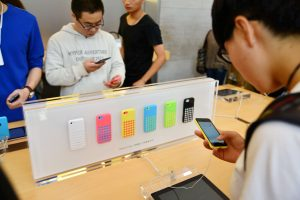 Customers try out smartphones at a mobile phone store (Photo: Reuters).