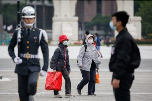 Tourists wear protective face masks to protect themselves from COVID-19 while passing by a flag rising ceremony at Chiang Kai Shek Memorial Hall in Taipei, Taiwan, 11 March 2020 (Photo: Reuters/Ann Wang).