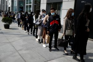 People wearing face masks, following the coronavirus disease (COVID-19) outbreak, make a line to enter an office building in Beijing, China is 28 April, 2020 (Photo: Reuters/Carlos Garcia Rawlins).