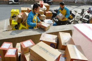 Workers of Chinese e-commerce retailer Suning Group sort out parcels at a distribution center of Suning in Nanjing city, east China's Jiangsu province, 13 November 2018.