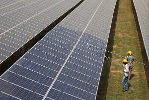 Workers clean photovoltaic panels inside a solar power plant in Gujarat, India, 2 July, 2015 (Photo: Reuters/Amit Dave).
