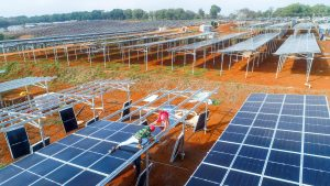 Workers labor on rows of solar panels that line in the field, Haikou city, south China's Hainan province, 28 February 2020 (Photo: Reuters).