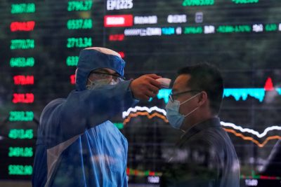 A worker wearing a protective suit takes body temperature measurement of a man inside the Shanghai Stock Exchange building, as the country is hit by a new coronavirus outbreak, at the Pudong financial district in Shanghai, China 28 February 2020 (Reuters/Aly Song).