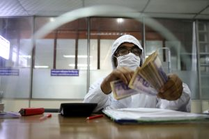 A government bank employee wears a protective suit while counting money amid the coronavirus disease (COVID-19) outbreak in Dhaka, Bangladesh, 2 April 2020 (Photo: REUTERS/Mohammad Ponir Hossain).