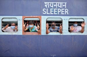 Migrant workers and pilgrims, who were stranded in the western state of Rajasthan due to a lockdown imposed by the government to prevent the spread of coronavirus disease (COVID-19), gesture from inside a train upon their arrival in their home state of eastern West Bengal, at a railway station on the outskirts of Kolkata, India, 5 May, 2020 (Photo: Reuters/Rupak De Chowdhuri).