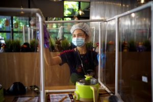A worker cleans a plastic barrier after customers had lunch at the Penguin Eat Shabu hotpot restaurant that reopened after the easing of restrictions with the implementation of a plastic barrier and social distancing measures to prevent the spread of the coronavirus disease (COVID-19) in Bangkok, Thailand, 8 May, 2020 (Photo:Reuters/Athit Perawongmetha).