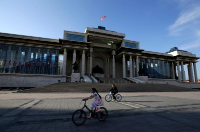 People cycle past the parliament building at Genghis Square in Ulaanbaatar, Mongolia (Photo: Reuters/Jason Lee).