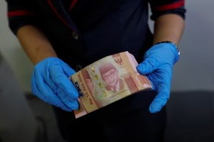 An employee wears synthetic gloves as she counts Indonesia's rupiah banknotes amid the spread of coronavirus disease (COVID-19) in Jakarta, Indonesia, 19 March 2020 (Photo: REUTERS/Willy Kurniawan).