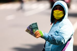 A currency exchange service vendor wearing a protective face mask while waiting for consumers on the sidewalk in Bandung, Indonesia, 22 May 2020. (Photo: Agvi Firdaus/INA Photo Agency/Sipa via Reuters).