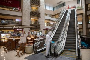 A janitor wearing a hazmat suit to prevent the spread of the coronavirus disease (COVID-19) cleans the rails of an escalator in an almost empty shopping mall in Mandaluyong City, Metro Manila, Philippines 3 June 2020 (Photo: Reuters/Eloisa Lopez).