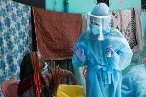 A healthcare worker wearing personal protective equipment (PPE) speaks to a resident about the coronavirus disease (COVID-19) at a check up camp in Dharavi, one of Asia's largest slums, Mumbai, India, 7 June 2020 (Reuters/Francis Mascarenhas).