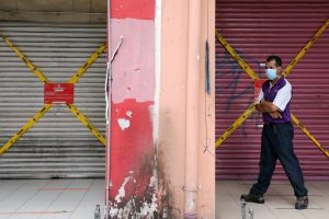 A man wearing a protective mask walks past closed shops amid the COVID-19 outbreak in Kuala Lumpur, Malaysia, 28 May 2020 (Photo: Reuters/Lim Huey Teng).