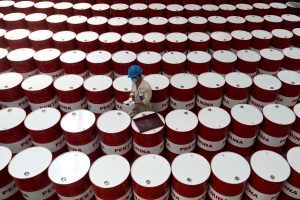A worker prepares to label barrels of oil at the state oil company Pertamina's production facility in Cilacap, Central Java, Indonesia, 6 November 2017 (Photo: Antara Foto/Rosa Panggabean via Reuters).