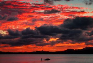 A Fijian family board their canoe as a sunset lights up the sky behind an island's mountain range in Suva 28 April, 2004 (Photo: Reuters/Gray).