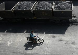 A worker rides his motorcycle near lorries transporting coal at a port of the Cua Ong Coal Preparation Company in Cam Pha town, Quang Ninh, Vietnam (Photo: Reuters/Kham).