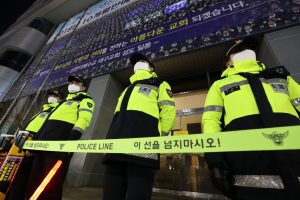Police officers form a police cordon in front of the Jesus Shincheonji Church in Daegu, about 300 kilometers southeast of Seoul. The church, in the center of the largest group infection in the country, has been subject to an administrative review by the authorities, Daegu, South Korea, 12 March 2020 (Reuters).