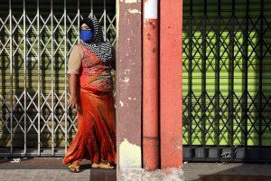 A Rohingya woman a wearing protective mask walks past closed shops amid the COVID-19 outbreak in Kuala Lumpur, Malaysia, 18 May 2020 (Photo: Reuters/Lim Huey Teng).